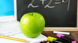 green apple on laptop ,old book and blackboard, selective focus